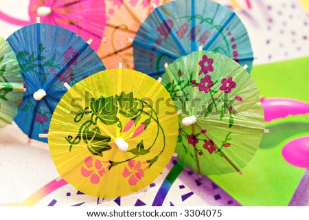 Drink umbrellas grouped on a colorful background. - stock photo