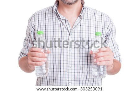 Drink water during summer heat concept with man holding two bottles isolated on white - stock photo