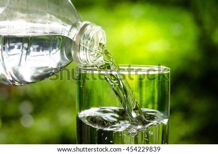 Drink water pouring in to glass over sunlight and natural green background
