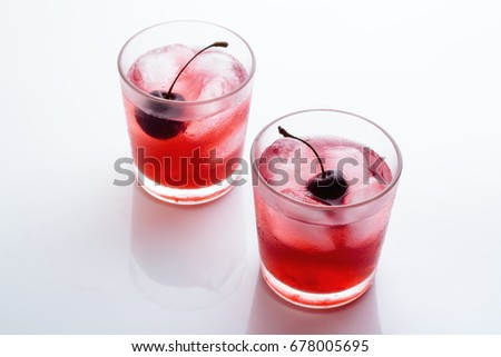 Drink with a cherry in a glass with ice on a white background