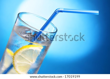 Drink with ice cubes and lemon slice close-up - stock photo