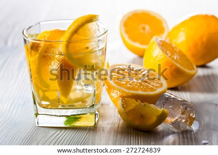 drink with lemon and ice on  old wooden table