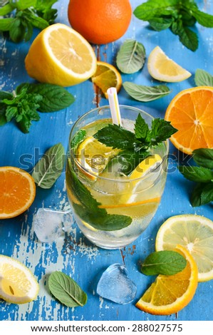 Drink with lemon, orange and mint in glass with ice - stock photo