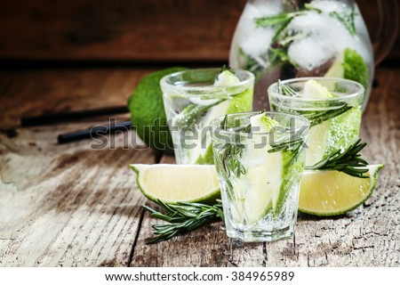 Drink with lime, rosemary, honey and soda, pitcher with crushed ice on the old wooden background, selective focus - stock photo