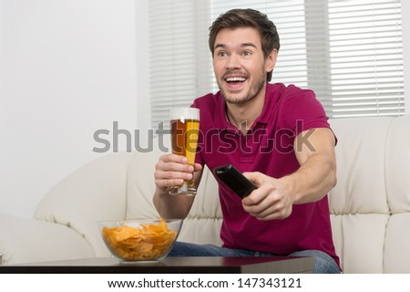 Drinking beer and watching TV. Cheerful young men drinking beer and holding a remote control in his hand - stock photo
