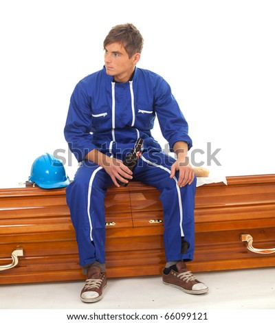 drinking beer gravedigger in blue overalls with hat sits on coffin