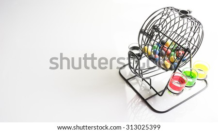 Drinking bingo metal cage with colorful lottery balls and cup of glasses. Isolated on white background. Slightly de-focused and close-up shot. Copy space. - stock photo