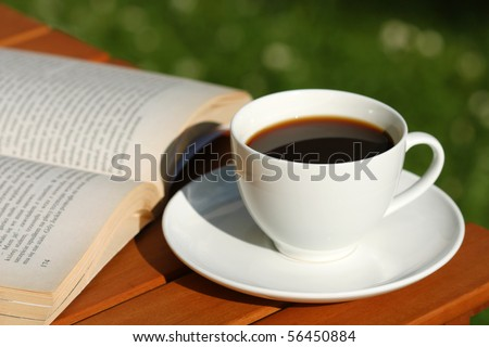 Drinking black strong coffee in the garden and reading book - stock photo