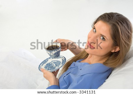 drinking coffee in the bed female looks up - stock photo