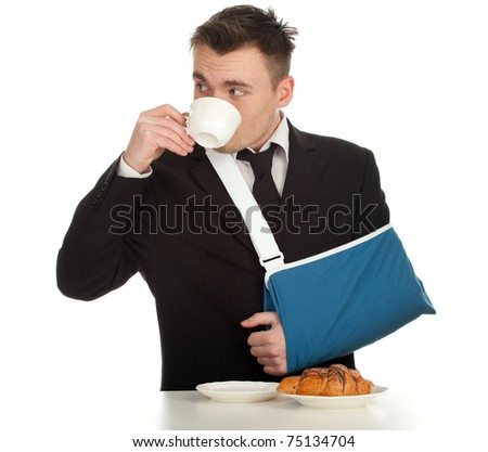 drinking coffee young businessman with broken hand wearing an arm brace, series - stock photo