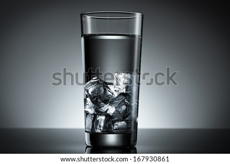 Drinking glass filled ice cube water top lighted - stock photo