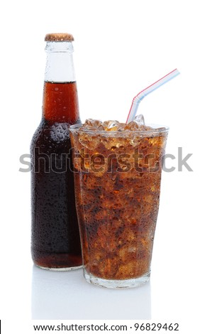 Drinking glass filled with ice cubes and cola soda with a capped bottle tucked in behind over a white background. - stock photo