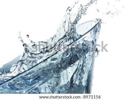drinking glass with clear fluid splashing out and around
