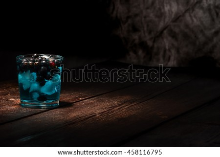 Drinking glass with ice cubes, black currant berries and blue liquid on the dark wooden surface.