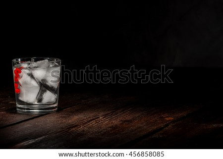 Drinking glass with ice cubes red currant berries and clear liquid on the dark wooden surface. - stock photo