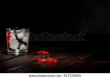 Drinking glass with ice cubes^ red currant berries and clear liquid on the dark wooden surface. - stock photo