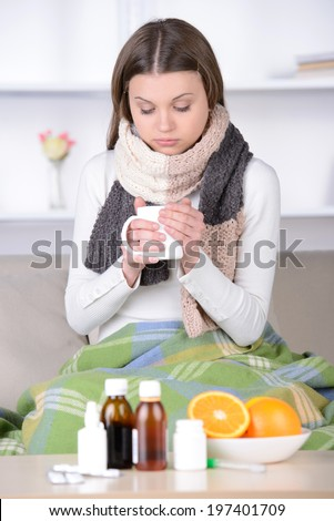 Drinking hot tea. Young woman in scurf drinking hot tea while sitting at her apartment