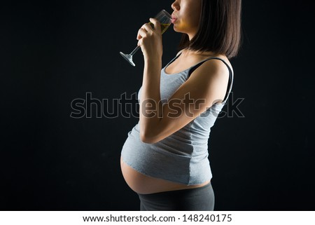 drinking pregnant mother on a over dramatic dark light background  - stock photo
