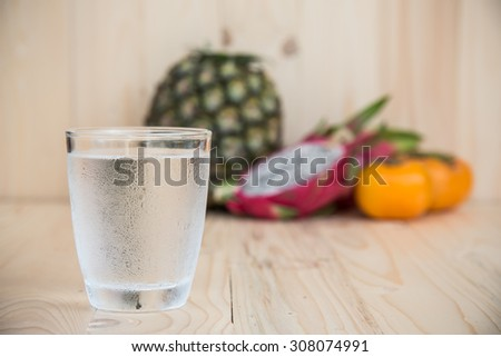 Drinking water and persimmon, dragon fruit, pineapple on wooden background - stock photo