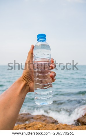 Drinking water bottle holding by hand   beside the sea. - stock photo
