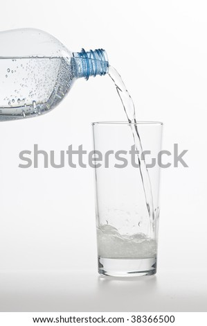 Drinking water flowing into a clear glass