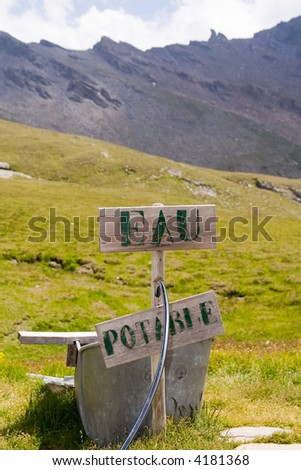 """Drinking-water fountain in the mountains with sign wich says """"eau potable"""" Drinking-water in french. - stock photo"""