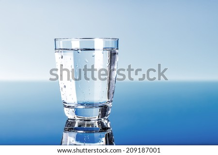 Drinking water in glass on blue - stock photo