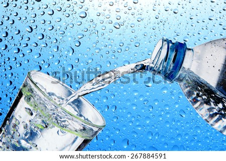 Drinking water is poured from a bottle into a glass - stock photo