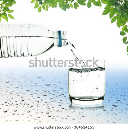 Drinking water is poured from a bottle into a glass on white and water drop background with clipping path
