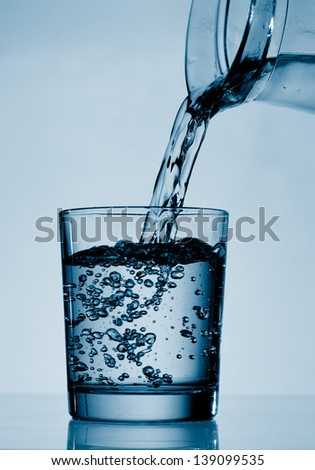 Drinking water is poured from a jug into a glass