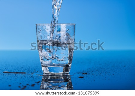 Drinking water is poured into a glass - stock photo