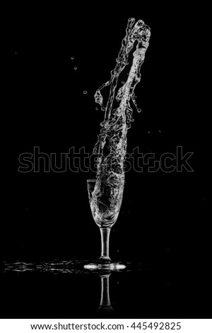 drinking water splash out of glass on black background.