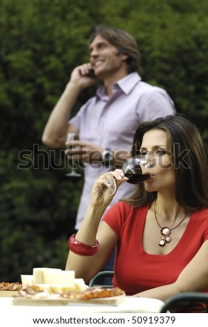 Drinking wine and talking with mobile phone - stock photo