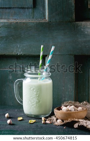 Drinking yogurt with pistachios served in glass mason jar with cocktail tubes and bowl of nuts on old wooden table. Dark rustic style. - stock photo