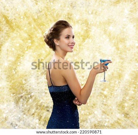 drinks, christmas, holidays and people concept - smiling woman in evening dress holding cocktail over yellow lights background yellow lights background - stock photo