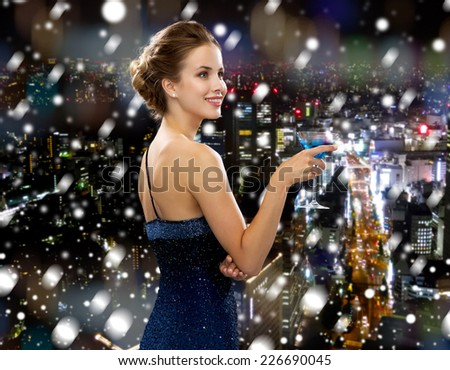drinks, christmas, holidays and people concept - smiling woman in evening dress holding cocktail over snowy night city background - stock photo