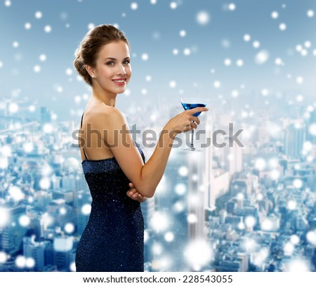 drinks, holidays, christmas, people and celebration concept - smiling woman in evening dress holding cocktail over snowy city background - stock photo