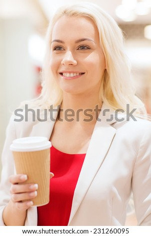 drinks, lifestyle, leisure and people concept - happy young woman with coffee paper cup in mall - stock photo