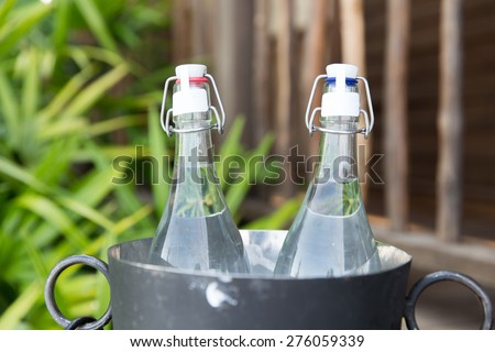 drinks, thirst, refreshment and summer resort concept - couple of water bottles in ice bucket at hotel - stock photo