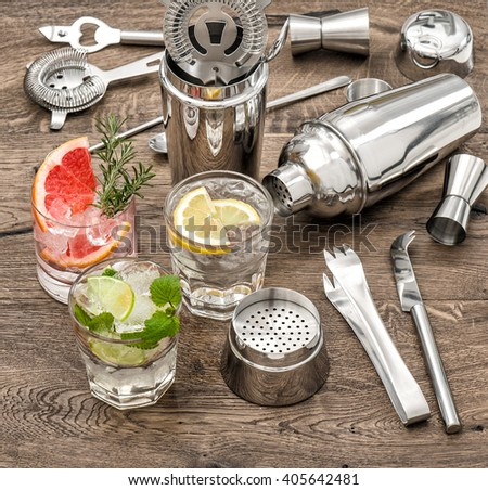 Drinks with ice and tonic water. Cocktail making bar accessories, shaker, glasses, mint leaves - stock photo