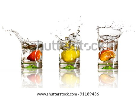 Drinks with splashing citrus fruits over white - stock photo