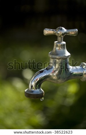 Dripping faucet in garden on green background - stock photo