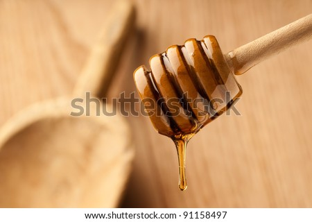Dripping honey surrounded by warm wood and soft light - stock photo