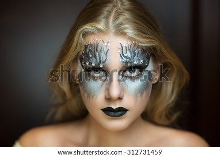 Dripping silver paint on pretty woman face. Art make up idea for Halloween, emotional photo good for party banner, blog, music album or magazine. Fairy tale, future party go-go, disco techno club.  - stock photo