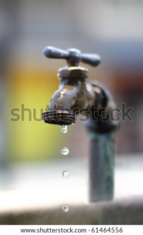 dripping water on an old faucet.narrow DOF - stock photo