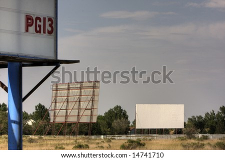 Drive in movie theater with two screens and PG13 film rating sign somewhere in the southwest. HDR image. Copy space. - stock photo