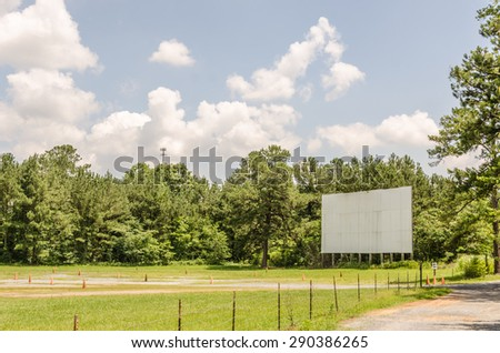 Drive-in theater movie screen that looks quite lonely without the speakers