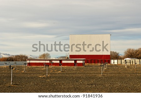 Drive-in theater with a bright white and red screen, dirt parking area, and speakers on posts just waiting for warmer weather - stock photo