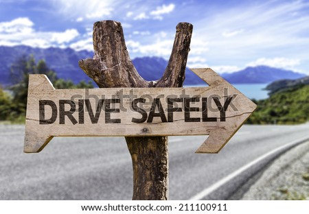 Drive Safely wooden sign with a street background  - stock photo