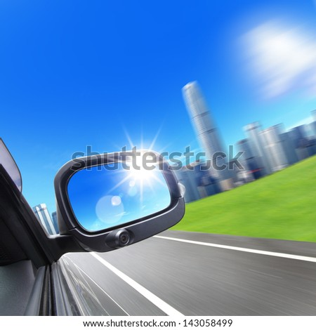Drive to city, car and rear view mirror on the road, concept for business, speed or success - stock photo